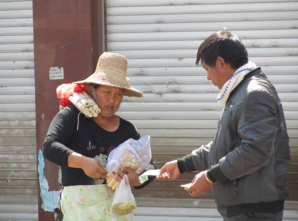 Buying bamboo stuffed with sticky rice, Xisuangbanna,  February 2011