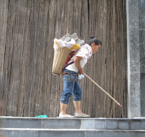 Female building worker with walking stick, Guiyang, China. Aug 2013