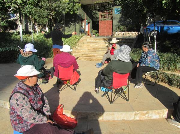Old women enjoy the winter sunshine and knit and sew.